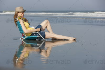 A woman in a sunhat and scarf on the beach, sitting holding a digital tablet,