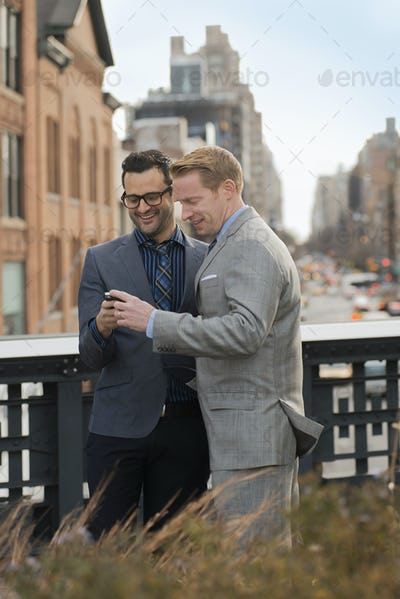 Two men in formal business clothes looking at a cell phone screen