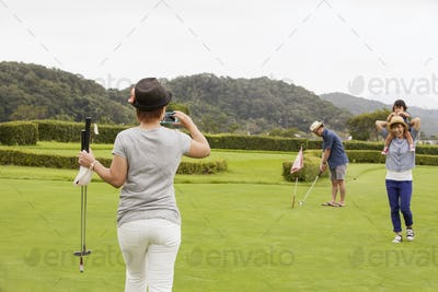 Family on a golf course.A child and three adults. a woman with a camera.
