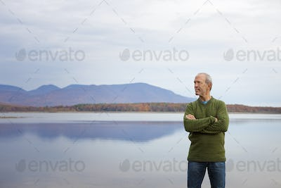 A man with arms folded by the water of a flat calm lake in the mountains.
