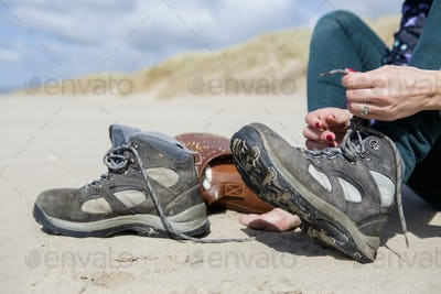 Young woman taking her hiking boots off on the beach at Harlech.