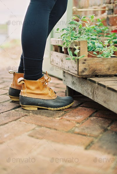 A woman wearing waterproof boots, with a box of seedlings.