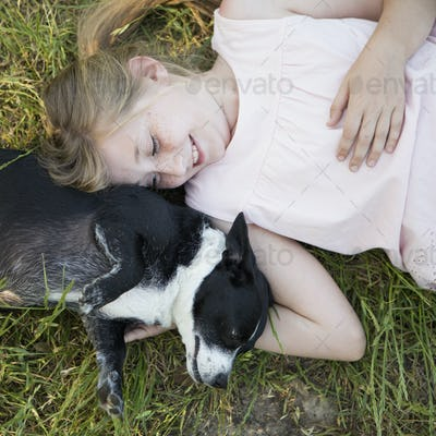 A girl hugging a black and white dog in the park.