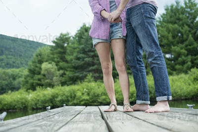 A couple on a wooden jetty by a lake.
