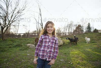 A child, a young girl in the goat paddock enclosure at an animal sanctuary.