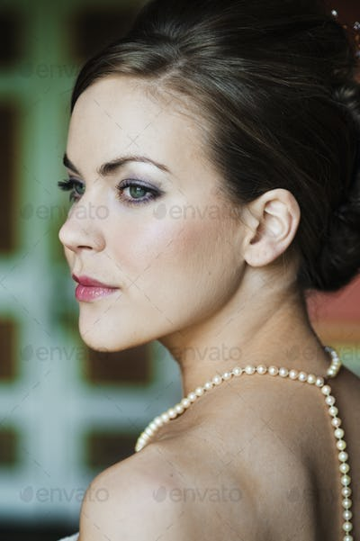 A woman with brown hair, wearing a pearl necklace.