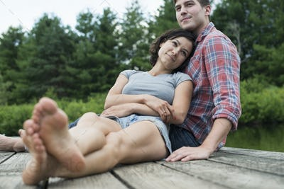A couple relaxing on a jetty overlooking a mountain lake.