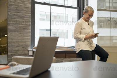 Office life.A woman seated on the edge of her desk using a digital tablet.