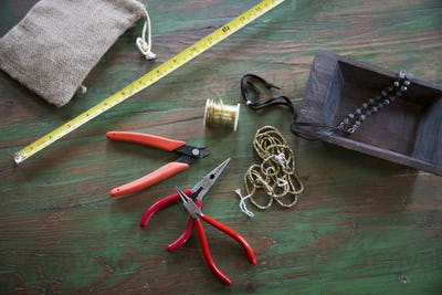 A tabletop with jewellery making equipment. Pliers, thread and a wooden tray, with measuring tape.