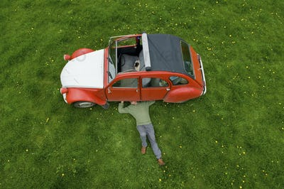 A man lying on his back under a red car, inspecting the underside of the car.