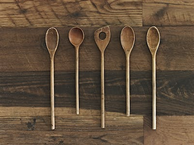 Home cooking. A wooden table with a varied wood grain and colour. Five wooden spoons in a row.