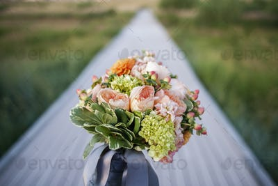 A long narrow table, with a bunch of fresh flowers in a blue vase. Table decoration.