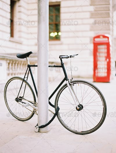 A bicycle chained and locked to a lamppost on street,  red public telephone box in the background,
