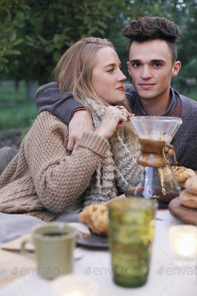 Apple orchard. A couple embracing, food and drink on a table.