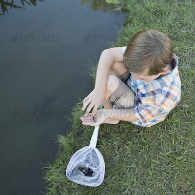 A young boy sitting on a river bank, examining a small fish, a tiddler he scooped up in a net.