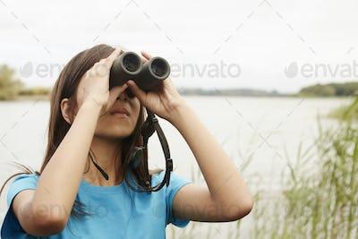 A young girl, a birdwatcher with binoculars.