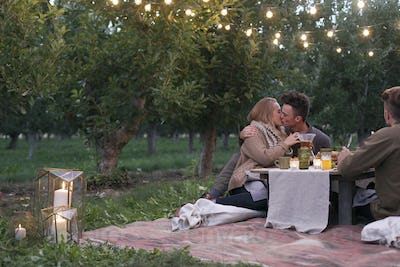 Apple orchard. Couple sitting on the ground, kissing, food and drink on a table.