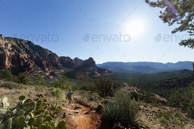 A woman in a sunhat walking up a trail hiking in the midday sun, mountain landscape