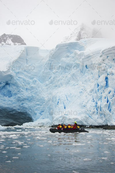 People in small inflatable zodiac rib boats passing icebergs and ice floes in the Antarctic