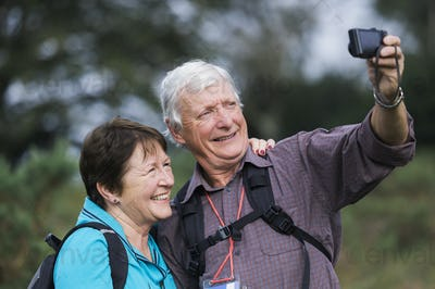 A mature couple taking a selfy photograph while out walking.