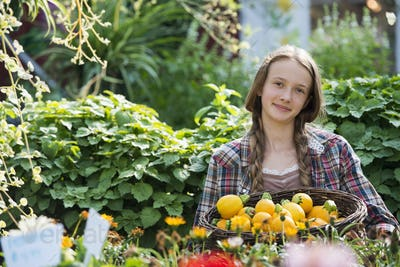 Summer on an organic farm. A girl holding a basket of fresh squash vegetables.