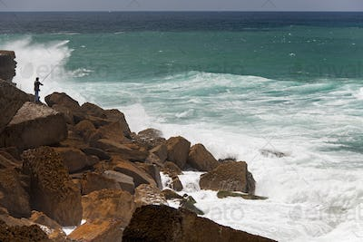 A fisherman standing on the rocks surf casting in the white waves on the Antlantic coast.