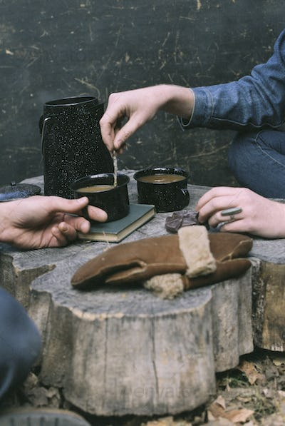 Couple having coffee in a forest, mugs and coffee pot, a pair of gloves on a tree trunk