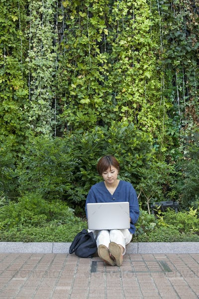 A woman with a laptop sitting outdoors.