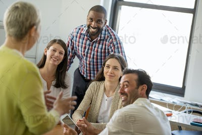 Five people in an office, two men and three women talking.