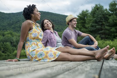 A group of people sitting on a woode pier overlooking a lake.