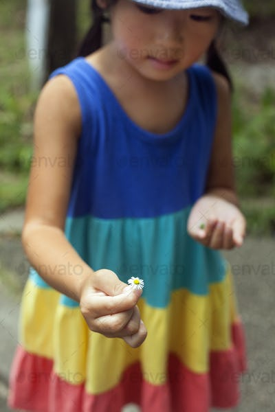 Young girl wearing a summer dress, holding a flower.