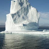 A tall iceberg on the waters of the shore of Greenland.
