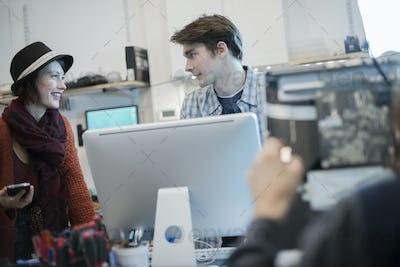 Computer Repair Shop. A man and woman talking over a computer.