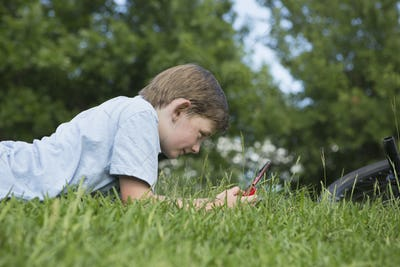 A young boy lying on the grass playing a hand held electronic game.