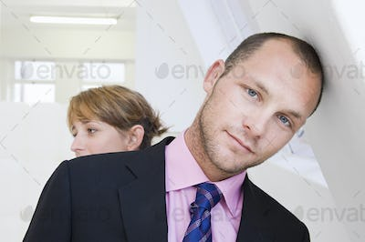 A young man in a suit and pink shirt, leaning against a wall, and a young woman in the background.