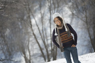 Winter scenery with snow on the ground. A young woman wearing a woolley hat.