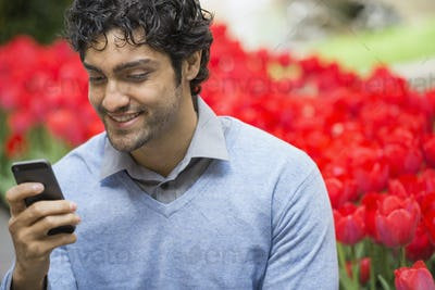 A man in a park, using his mobile phone, bed of red flowering tulips in the background,