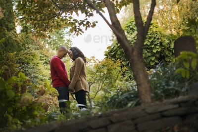 City park with trees, A man and a woman, a couple holding hands,
