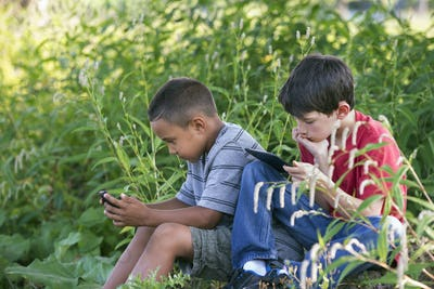 Two boys sitting in a field, one on a smart phone and one using a digital tablet.