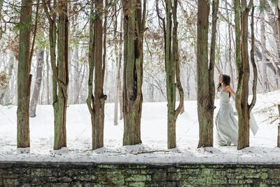 A woman in a ball gown outdoors in the snow.