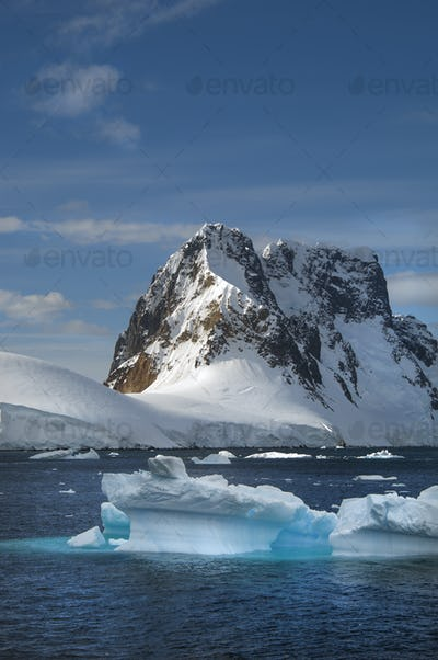 Icebergs floating in the water off the rocky shore of Antactica.