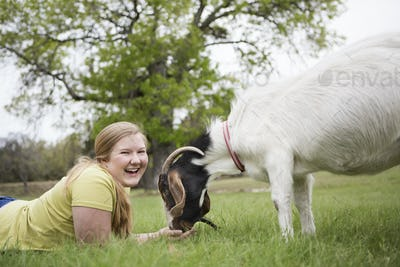 A girl lying on grass head to head with a goat.