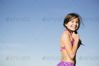A young child in a bikini with plaited hair.