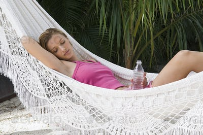A woman relaxing in a hammock holding a bottle of water.