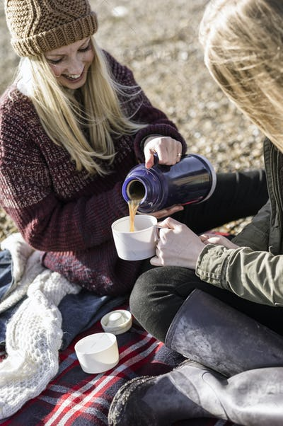 Two girls having a winter picnic on the beach.