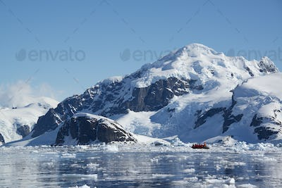 A small boat floating on the ocean among ice floes, off the shore of an island in Antarctica.