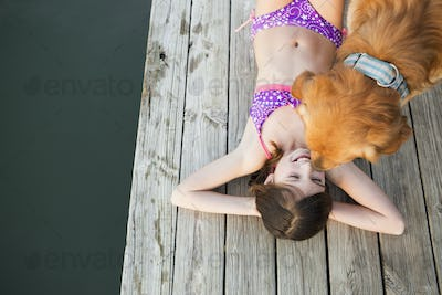 A young girl and a golden retriever dog on a jetty.