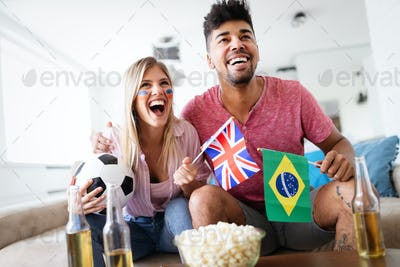 Couple, sports, entretainment and happiness concept. Happy couple cheering at home