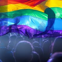 Colorful LGBT flag blows in the breez over crowd.
