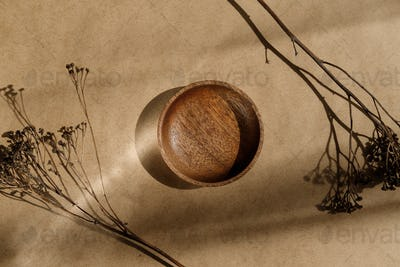 Top view of an empty wooden bowl decorated dry grass. Beige or sand tones